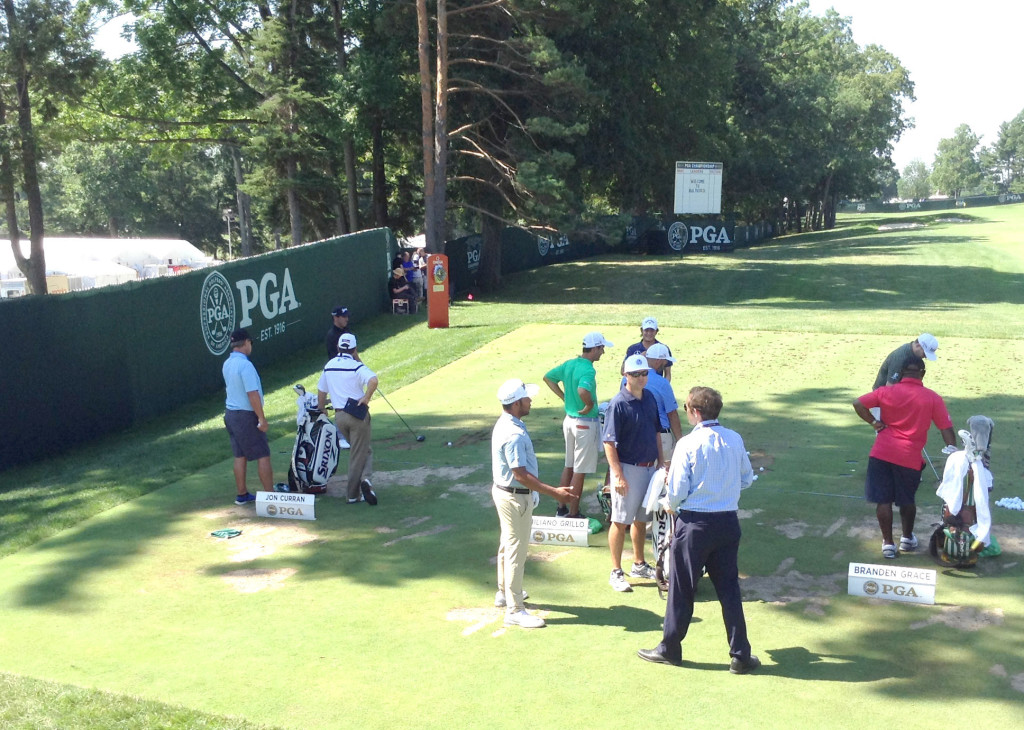 Harold Varner III, 4th from left talking with his caddie and friend on driving range.