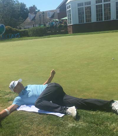 Brendan Steele stretches out on the putting green, pre-round.