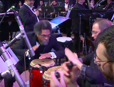 Dr. West plays congas on stage during the musical tribute.