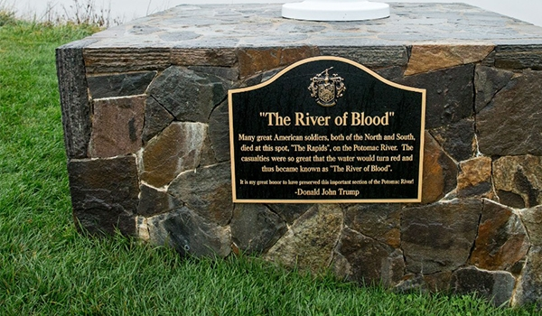 "A plaque that reads ""The River of Blood"" sits at the base of a flagpole between the 14th and 15th hole at the Trump National Golf Club in Sterling, Va., Wednesday, Dec. 2, 2015. The historical accuracy that ""American soldiers, both of the North and South, died at this spot"" has been called into question by historians."